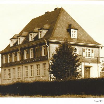 Anfang der dreißiger Jahre des vorigen  Jahrhunderts wurde die zweiklassige Volks-  schule mit Lehrerwohnung eingeweiht. Das  imposante Gebäude wurde Mitte der siebziger  Jahre zum Kindergarten umgebaut. Vor dem  Bau dieser Schule besuchten die Kinder des  Schulverbandes die alte Schule in Fladersbach.