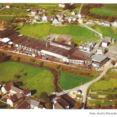 Das Luftbild zeigt die Firma Karl Georg Ende der  fünfziger Jahre. Die große Produktionshalle entlang  der Bundesstraße wurde nach dem 2 Weltkrieg gebaut.  Damals wie heute werden in Neitersen Eisenbahnpuffer  hergestellt.  Im Hintergrund ist der Ortsteil Fladersbach zu sehen.